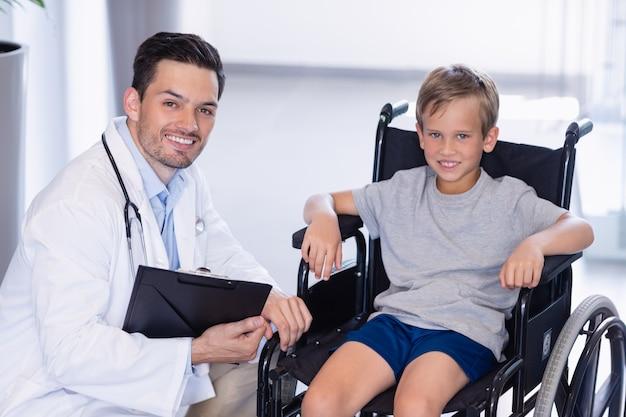 Het portret van glimlachende arts en maakt jongen in gang onbruikbaar