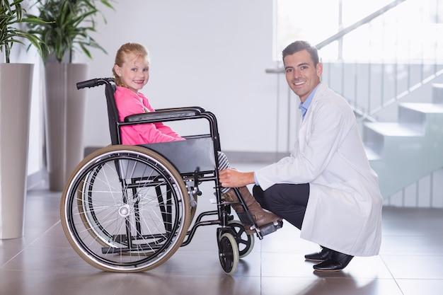 Het portret van glimlachende arts en maakt meisje onbruikbaar