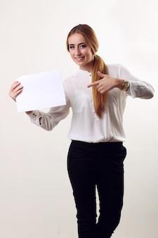 Het portret van glimlachende bedrijfsvrouw met vinger toont het document, dat op witte muur wordt geïsoleerd