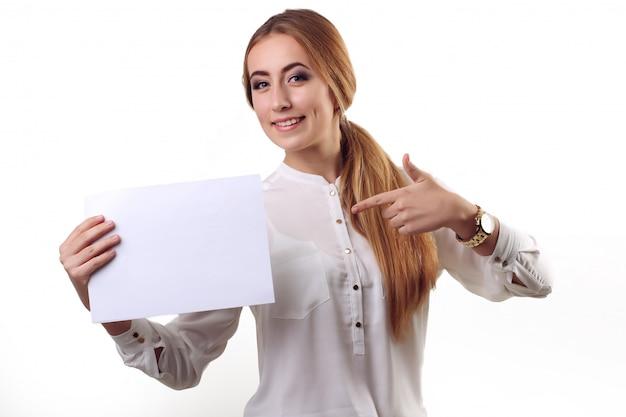 Het portret van glimlachende bedrijfsvrouw met vinger toont op papier, dat op witte muur wordt geïsoleerd