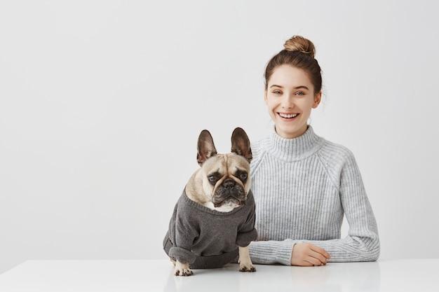 Het portret van glimlachende donkerbruine vrouw met haar bond topknot thuis werkend bureau vast. vrouwelijke freelancerzitting bij de lijst in workshop in gezelschap van hond. vriendschap concept