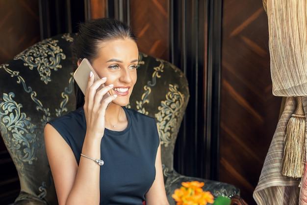 Het portret van glimlachende jonge vrouw spreekt thuis op smartphone in de leunstoel