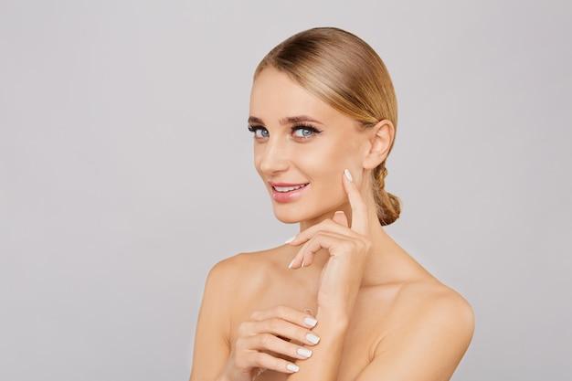 Het portret van glimlachende mooie blondevrouw met natuurlijk maakt omhoog wat betreft haar gezicht.