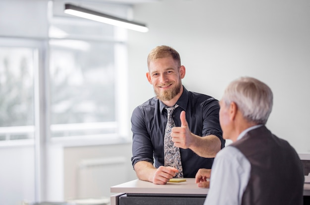 Het portret van glimlachende zakenman die duim toont ondertekent omhoog in het bureau