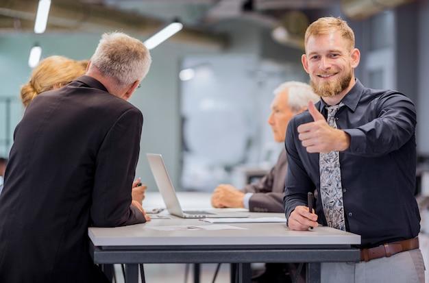 Het portret van glimlachende zakenman die duim toont ondertekent omhoog terwijl team die op de achtergrond bespreken