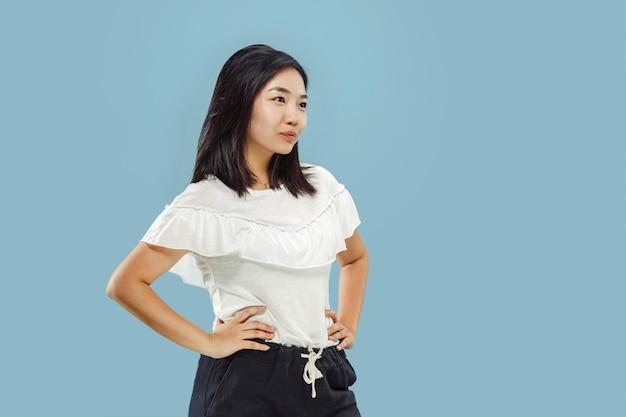 Het portret van halve lengte van de koreaanse jonge vrouw op blauwe achtergrond