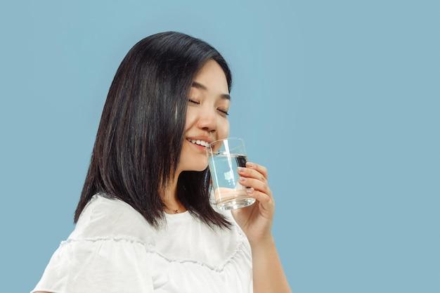 Het portret van halve lengte van de koreaanse jonge vrouw op blauwe ruimte. vrouwelijk model in wit overhemd. genieten van drinkwater.