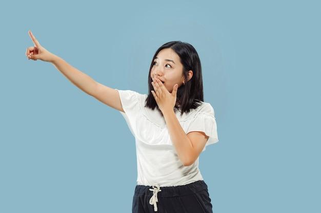 Het portret van halve lengte van de koreaanse jonge vrouw op blauwe ruimte. vrouwelijk model in wit overhemd. iets laten zien en wijzen.
