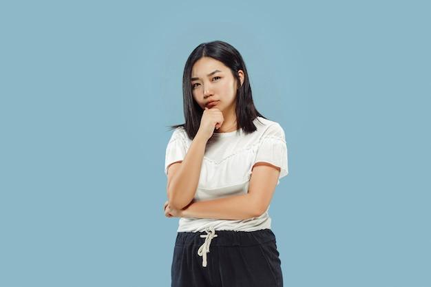 Het portret van halve lengte van de koreaanse jonge vrouw op blauwe ruimte. vrouwelijk model in wit overhemd. nadenkend, ziet er serieus uit.