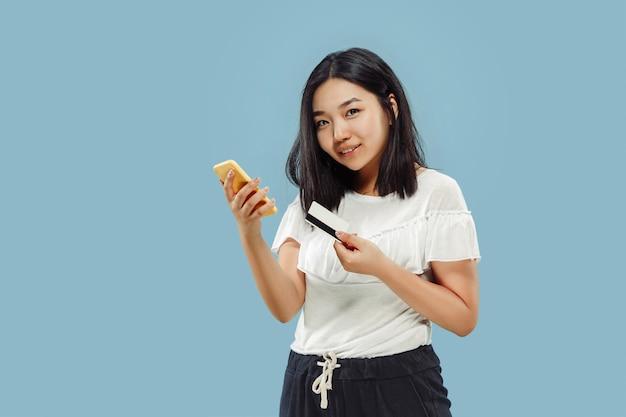 Het portret van halve lengte van de koreaanse jonge vrouw. vrouwelijk model dat haar smartphone gebruikt voor het betalen van rekening of online kopen. concept van menselijke emoties, gezichtsuitdrukking. vooraanzicht.