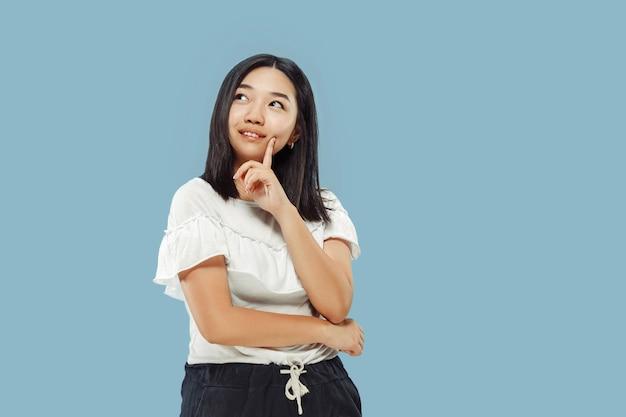 Het portret van halve lengte van de koreaanse jonge vrouw. vrouwelijk model in wit overhemd. denken en glimlachen. concept van menselijke emoties, gezichtsuitdrukking. vooraanzicht.