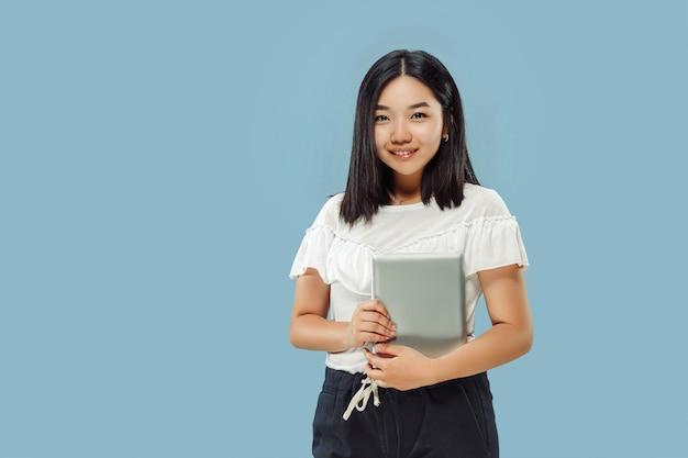 Het portret van halve lengte van de koreaanse jonge vrouw. vrouwelijk model in wit overhemd. een tablet vasthouden en glimlachen. concept van menselijke emoties, gezichtsuitdrukking. vooraanzicht.