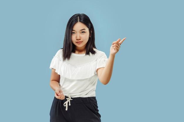 Het portret van halve lengte van de koreaanse jonge vrouw. vrouwelijk model in wit overhemd. iets laten zien en wijzen. concept van menselijke emoties, gezichtsuitdrukking. vooraanzicht.