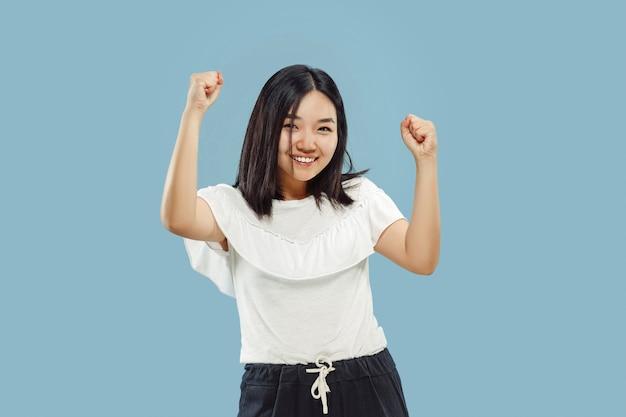 Het portret van halve lengte van de koreaanse jonge vrouw. vrouwelijk model in wit overhemd. vieren als een winnaar, ziet er gelukkig uit. concept van menselijke emoties, gezichtsuitdrukking. vooraanzicht.
