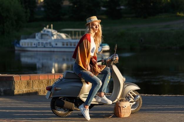 Het portret van het aantrekkelijke meisje. dame in jeans, kort t-shirt en strohoed zittend op een retro bromfiets in de buurt van de rivier bij zonsondergang. reisconcept.