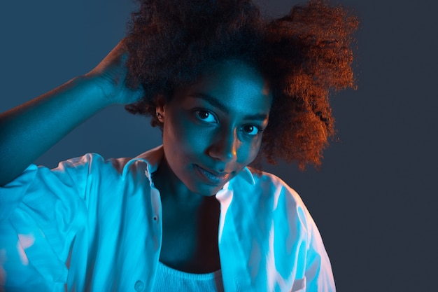 Het portret van het afrikaanse jonge meisje op zwart blauw in roze neonlicht
