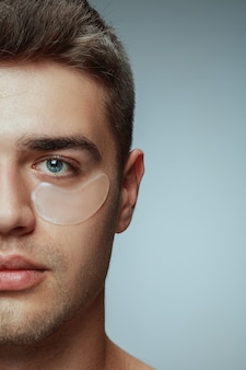 Het portret van het close-upprofiel van de jonge mens die op grijze studioachtergrond wordt geïsoleerd. mannelijk gezicht met collageenvlekken onder de ogen. concept van de gezondheid en schoonheid van mannen, cosmetologie, lichaams- en huidverzorging. anti-veroudering.