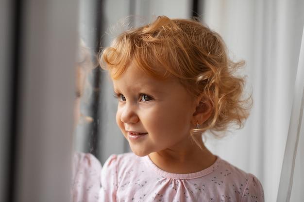 Het portret van het close-upprofiel van krullend kindmeisje thuis.