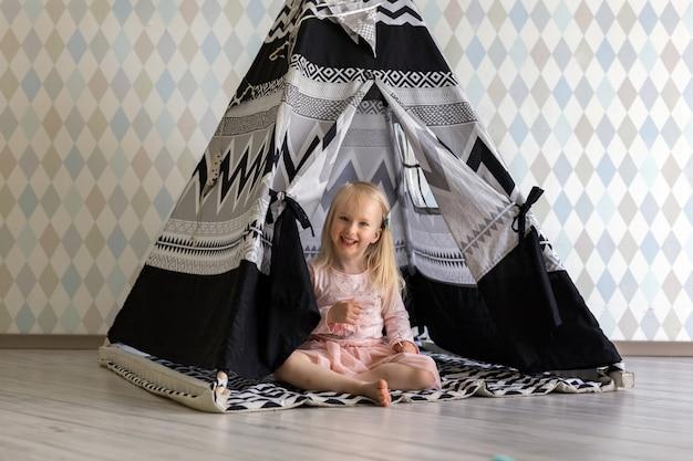 Het portret van het gelukkige 3-jarige meisje van het peutermeisje glimlachen terwijl het zitten in de tent van het kinderenspel