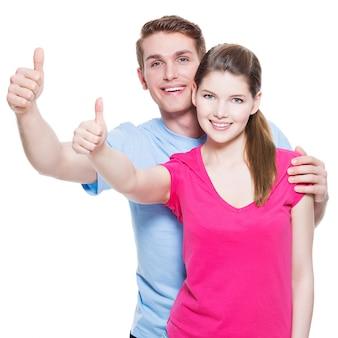Het portret van het gelukkige paar met duimen ondertekent omhoog dat op witte muur wordt geïsoleerd.