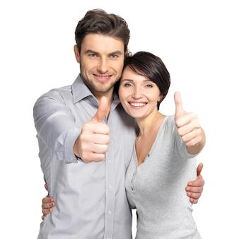 Het portret van het gelukkige paar met duimen ondertekent omhoog