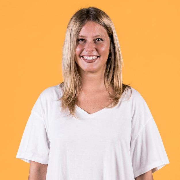 Het portret van het glimlachen schakelt vrouw status op gekleurde achtergrond uit