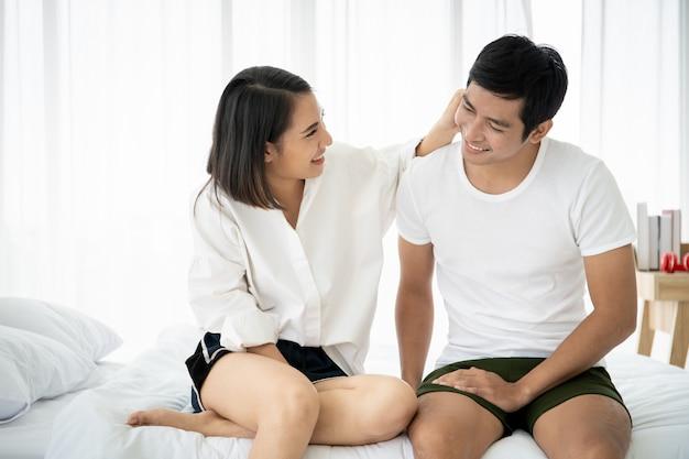 Het portret van het grappige en romantische aziatische paar in slaapkamer met natuurlijk licht van venster, concept relatie tussen echtgenoot en vrouw en het zijn een familie.