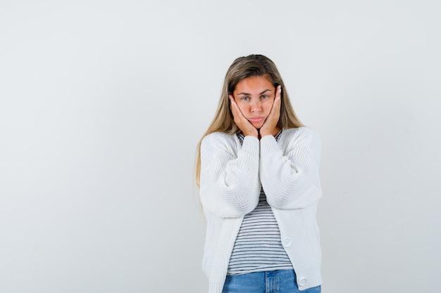 Het portret van het jonge dame hoofdkussen gezicht op haar dient t-shirt, jasje in en kijkt verontrust vooraanzicht