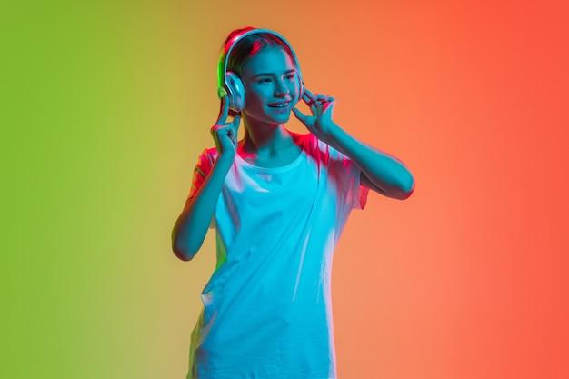 Het portret van het jonge kaukasische meisje op gradiënt groen-oranje in neonlicht