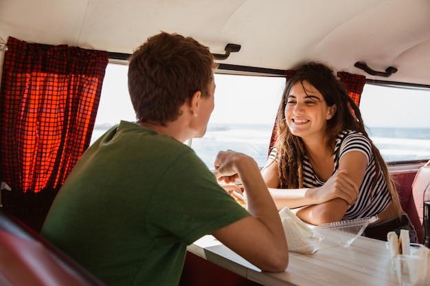 Het portret van het jonge paar glimlachen geniet van reis binnen minivan