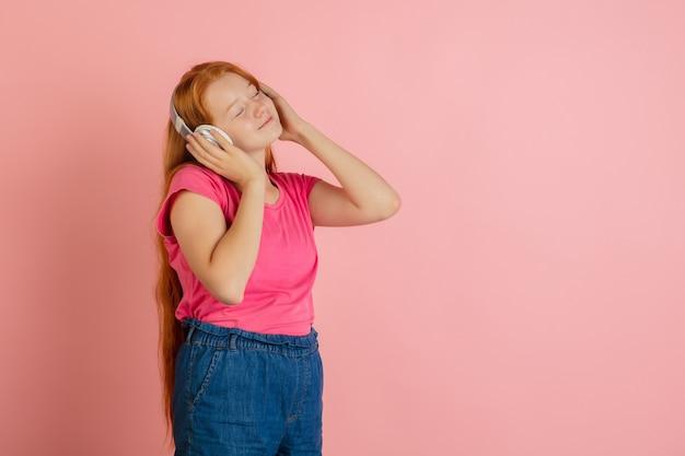 Het portret van het kaukasische die tienermeisje op koraal roze studio wordt geïsoleerd