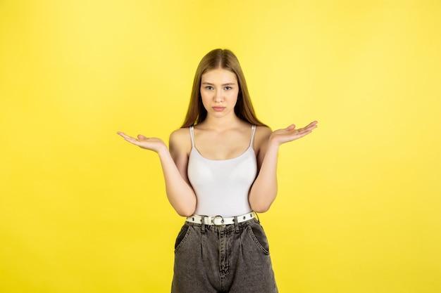 Het portret van het kaukasische jonge meisje dat op gele studio wordt geïsoleerd