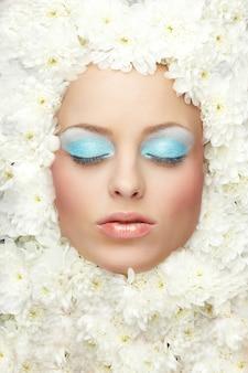Het portret van het model van de maniervrouw met heldere make-up ligt in bloemen