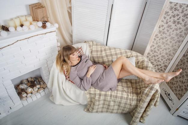 Het portret van het mooie blobde zwangere vrouw liggen en ontspant op de bank in slaapkamer. gelukkige zwangere vrouw zachtjes aanraken buik. zwangerschap en moederschap. 9 maanden gezondheid zwangere vrouw in afwachting van baby.