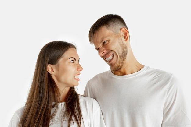 Het portret van het mooie jonge paar dat op witte muur wordt geïsoleerd. gelaatsuitdrukking, menselijke emoties, reclameconcept. man en vrouw staan, kijken elkaar boos aan.