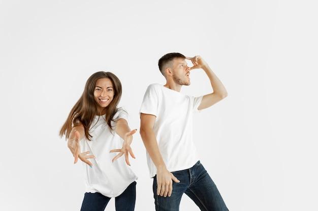 Het portret van het mooie jonge paar dat op witte ruimte wordt geïsoleerd. gelaatsuitdrukking, menselijke emoties, reclameconcept. copyspace