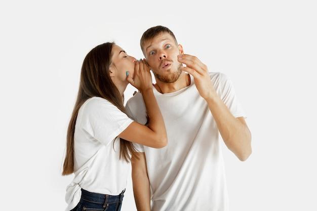 Het portret van het mooie jonge paar dat op witte studioachtergrond wordt geïsoleerd. gelaatsuitdrukking, menselijke emoties, advertentieconcept. man en vrouw fluisteren elkaar geheimen toe en bedekken het oor met de handpalm.