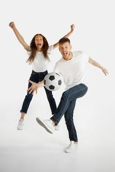 Het portret van het mooie jonge paar dat op witte studioachtergrond wordt geïsoleerd. gelaatsuitdrukking, menselijke emoties, reclame, weddenschappen, sportconcept. man en vrouw voetballen of voetballen in actie.