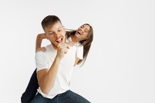 Het portret van het mooie jonge paar dat op witte studioachtergrond wordt geïsoleerd. gelaatsuitdrukking, menselijke emoties, reclameconcept. copyspace. vrouw en man dansen en zingen, zien er samen gelukkig uit.