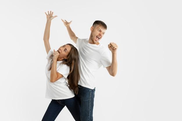 Het portret van het mooie jonge paar dat op witte studiomuur wordt geïsoleerd
