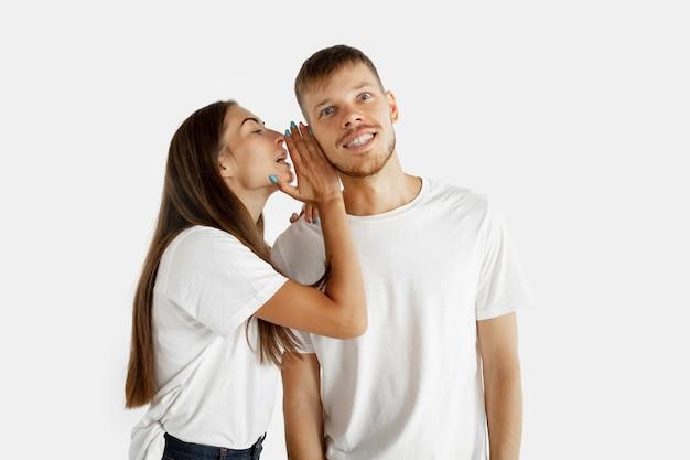 Het portret van het mooie jonge paar geïsoleerd. man en vrouw fluisteren elkaar geheimen toe en bedekken het oor met de handpalm.