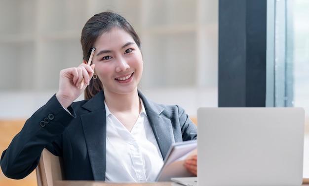 Het portret van het mooie potlood van de vrouwengreep raakt haar hoofd, glimlacht en bekijkt camera