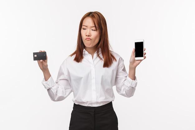 Het portret van het nadenken ernstig-uitziende jonge aziatische vrouw die keus maken, het mobiele telefoonscherm tonen en nadenkend creditcard bekijken, wil online product kopen, internet winkelend, beslissend