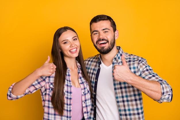 Het portret van het positieve vrolijke team van de echtpaarpromotor keurt advertenties goed