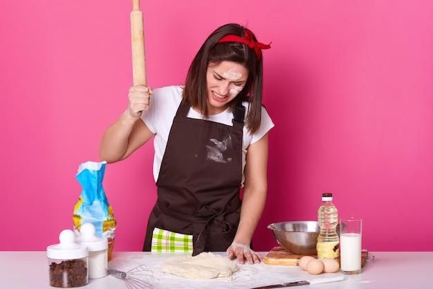 Het portret van jong brunette beklemtoonde wijfje die in keuken de hele dag werken, die eigengemaakt gebakje voorbereiden, kijkt vermoeid. slaat op deeg met houten deegroller met woede geïsoleerd op roos.