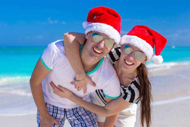 Het portret van jong paar in kerstmanhoeden geniet van strandvakantie