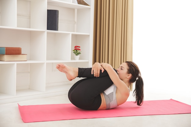 Het portret van jong sportief meisje die yoga doen stelt thuis