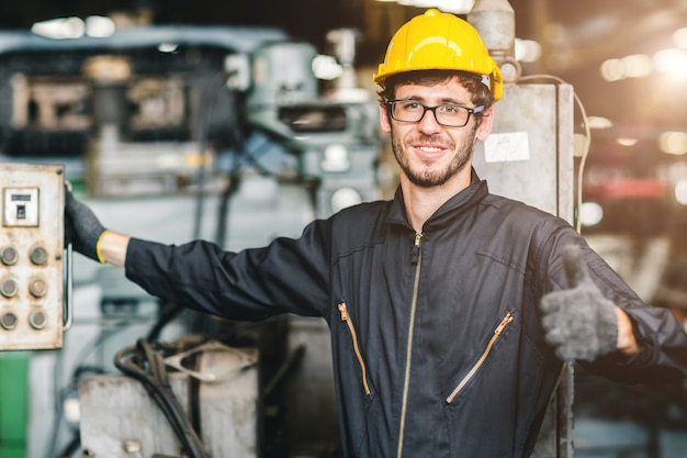 Het portret van jonge amerikaanse gelukkige arbeider geniet van het gelukkige glimlachen om in een zware industriële fabriek te werken. duim omhoog met machinecontrolemechanisme.
