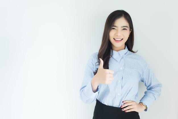 Het portret van jonge aziatische bedrijfsvrouw beduimelt omhoog zeer goed symbool op witte achtergrond.