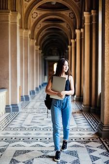 Het portret van jonge aziatische studente die laptop of een tablet in slim en gelukkig gebruiken stelt aan universiteit of hogeschool,